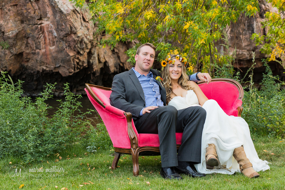 The bride & groom on a vintage red velvet couch at their Riverbend wedding